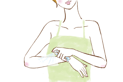 腕にスプレーをかける女性